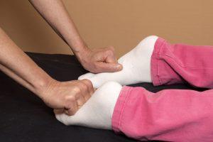 Terapeuten arbetar med patientens fotsulor.
