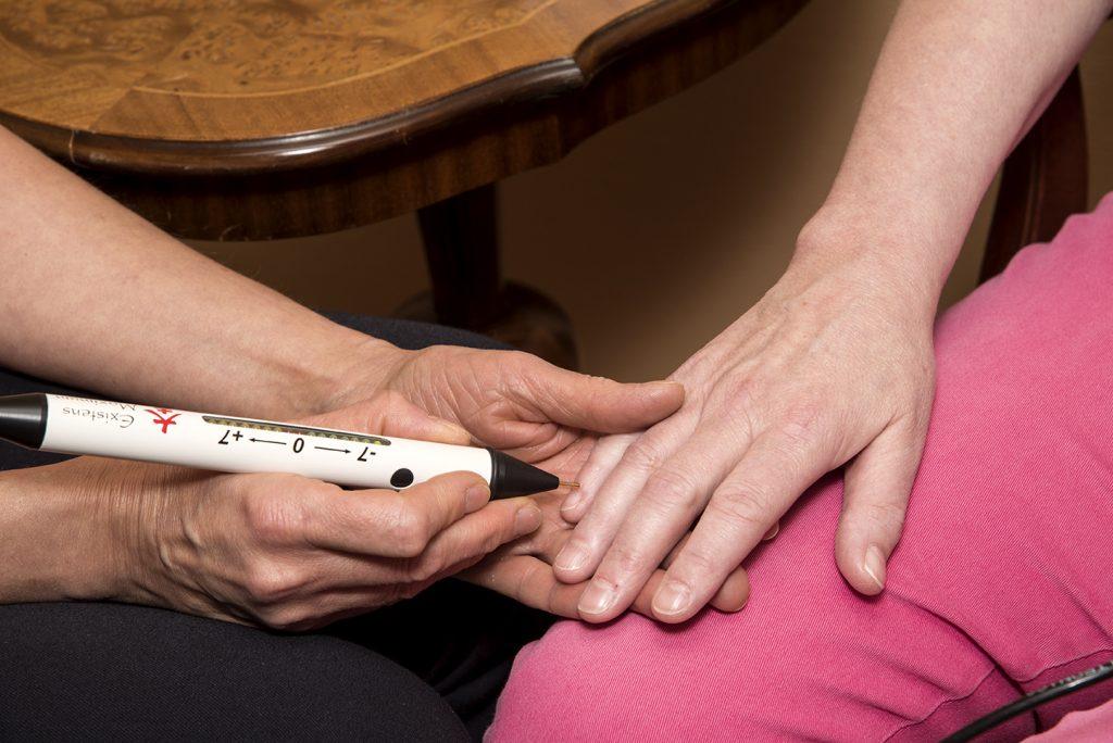 Terapeuten mäter energistatus med ett diagnosinstrument.